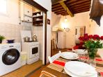 Kitchen with washing maschine, sink, gas, oven, dishes, glasses, cutley.