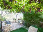 Enjoy relaxing in our garden under the grapevines..!