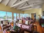 Light-filled great room has walls of windows, ocean views and hardwood floors.