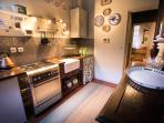 The kitchen includes a  oven/hob, microwave, fridge freezer and a washing machine