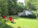 Sunny yard on the north side. Private & surrounded by tall trees & rhododendron.