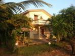 Sunset Sea View Beach Villa C12, surrounded by Palm trees & shaded patio area with cane furnitue