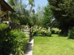 Garden view - an acre of garden to relax in with pond and loungers dotted around.