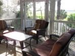 Screened in back deck with comfy seating for sunset watching, and also a picnic table for diningn