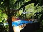 Pool surrounded by tropical fauna, has a covered cabana and picnic table overlooking the rivers.