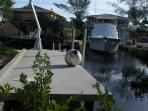 View of the boat dock that runs along side the 38 ft boat slip behind the house. Water and power.