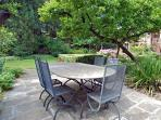 in the garden there is a large metal table with 8 chairs