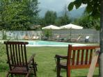 Pool situated in flat garden (which is now mature) with the village and mountains in the background.