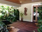 Ipe wood-covered entry with charming gold fish pond & lush foliage
