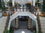 Dual wrought iron staircase and crystal chandelier in three story entrance foyer.