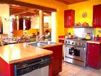 Commercial gourmet oven/range, butcher block counters, red enamel cabinets all create upscale southwest ambiance