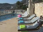 Teak sunbeds with pool towels and cushions