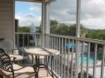 Southfacing screened balcony with view over the mangroves and the pool