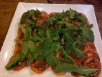 Healthy salad of tomato and rocket with balsamic vinaigrette.