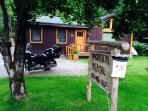 front of cabin with vacation rental sign by road
