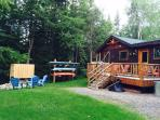 backyard with canoe/kayak rack, deck, furniture, gas grill, fire pit, stream & outdoor shower