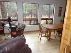 Dinning area with four chairs looking out to the tall pines