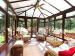 Beautiful conservatory overlooking river and leading to decked area.