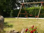 Set of swings with boules pitch behind, on side garden