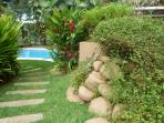 Lush gardens surround the pathway to the pool!