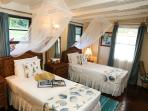 The twin room has two single beds, Each room has mosquito nets over the beds, fans and air con