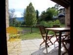 La terrasse couverte donne sur le jardin et le terrain de 1700 m2 (jeux et détente).