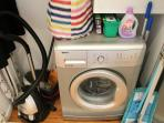 The washing machine is concealed in a cupboard