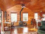 Open great room with high ceilings and wood-burning stove/fireplace