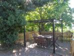 Outside dining area on decking with pergola, with views across the garden and vineyard valley