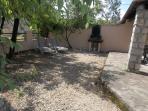 Cour fermée avec barbecue et salon de jardin