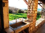 an outdoor sink next to the summer kitchen
