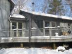 Front of house with snow, overlooking wooded acreage