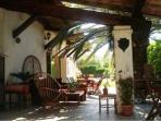 notre agréable terrasse ombragée sous immense palmier/tables&chaises pour la détente-et fumeurs....
