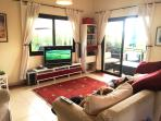 Bright and airy lounge, with large TV, DVD player, with surround sound, playstation, books, DVD.s to