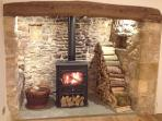 One of two original inglenook fireplaces in the cottage, each with a log burning stove.