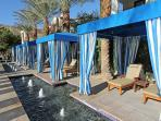 Family pool area with beach style entry, cabanas, and fountains.