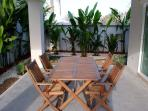 Cool and breezy outdoor dining area surrounded by exotic plants and rockery