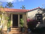 Nestled in tall shrubs and hedges with towering palms surrounding the property