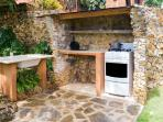 Outdoor cooking area with stove/oven and sink.