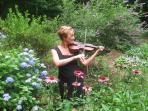 Deborah performing in front flower garden, before wedding.