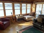 Relax in the cozy chaise or red leather swivel bucket chair while over-looking the lake.