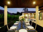 Dining table adjacent to swimming pool, suitable for al fresco dining and BBQs