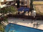 View from balcony overlooking the swimming pool & barbecue area