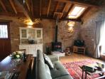 Converted barn open plan living area with leather suite (including sofa bed), TV and log burner