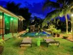 Nights view of swimming pool overlooking at tropical garden and paddy field