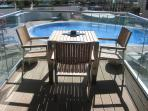 Lovely balcony with a table & 3 of the 4 chairs - overlooking the swimming pool