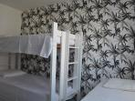En-suite room with bunk bed with trundle and a single bed, and air-conditioning