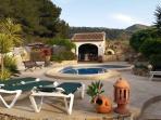 Terraza piscina amueblada con 4 tumbonas y sombrilla con la barbacoa enfrente.