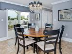 Oversized Circular Dining Table off Back Patio with Chandeliers