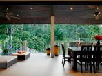 Spacious outdoor, undercover balcony with soft seating and dining table